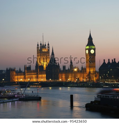 Westminster Palace, Big Ben and Victoria Tower, seen from Hungerford Bridge at Dusk - stock photo