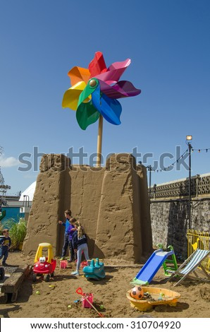 WESTON-SUPER-MARE, UK - AUGUST 26, 2015:  Children playing beside a giant sandcastle topped with a colourful windmill at the traditional seaside resort of Weston-Super-Mare, Somerset. - stock photo