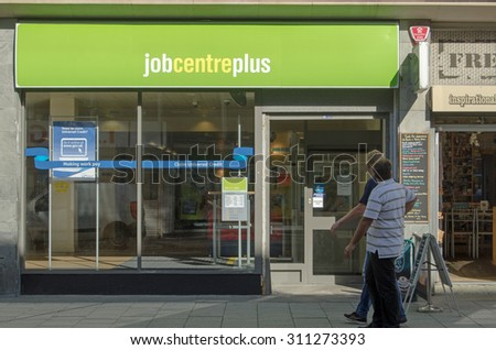 WESTON-SUPER-MARE, UK - AUGUST 26, 2015:  Two men walking past the Job Centre Plus government employment office in the centre of Weston-Super-Mare, Somerset on a sunny day in August.