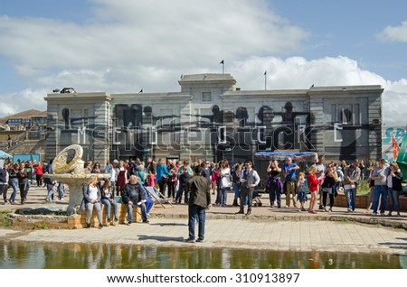WESTON-SUPER-MARE, UK - AUGUST 26, 2015:  Visitors crowding the 'mediocre' Dismaland theme park inspired by Banksy and erected in a disused swimming pool in the Somerset resort of Weston-Super-Mare.