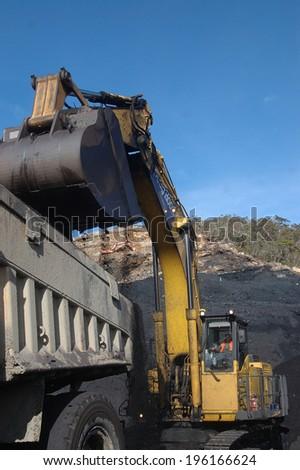 WESTPORT, NEW ZEALAND, CIRCA 2007: Digger loads up a truck with high grade coal at Stockton Coal Mine, West Coast, South Island, New Zealand - stock photo