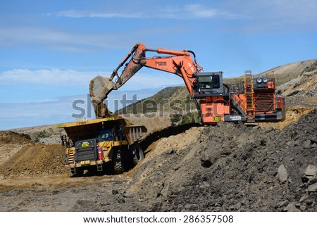 WESTPORT, NEW ZEALAND, MARCH 11, 2015: 190 ton digger loads rock from a layer of overburden at open cast coal mine on March 11, 2015 near Westport, New Zealand