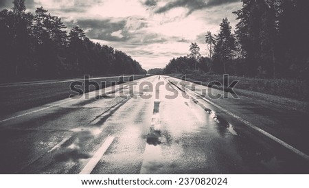wet asphalt road with sun reflections and trees - retro, vintage style look - stock photo