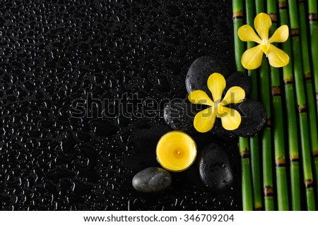 Wet background -beautiful three yellow orchid with black stones, candle on bamboo grove  - stock photo