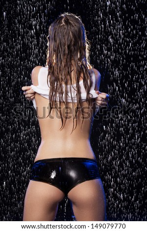 Wet beauty undressing. Rear view of beautiful young women in wet T-Shirt undressing under the rain - stock photo