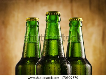 Wet beer bottles on rustic wooden background