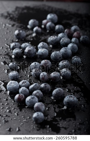 Wet blueberries on black slate - stock photo