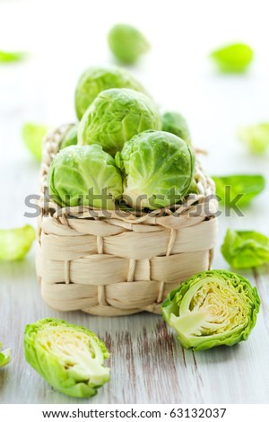 Wet brussels sprouts in basket on the white wooden table