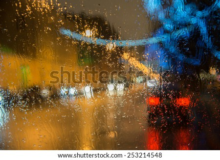 Wet cars window with  background of the night city lights - stock photo