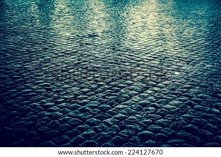 Wet cobblestone street at night - stock photo