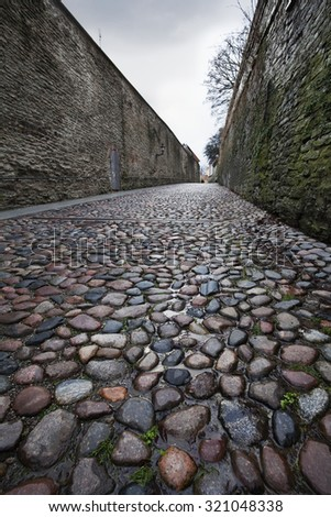 Wet cobblestones after rain on narrow street in the old town of Tallinn, Estonia - stock photo