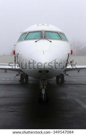 Wet cockpit of the medium sized white jet parked on the ramp