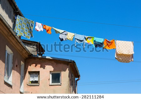 Wet colorful clothing is hanging on the cord. Old district of Klaipeda, Lithuania. - stock photo