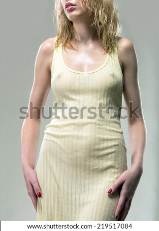 Wet dress fits snugly young girl, emphasizing all the advantages of her figure - stock photo