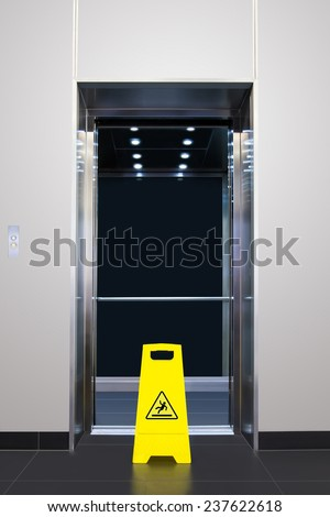 Wet floor caution sign in front of lift door - stock photo