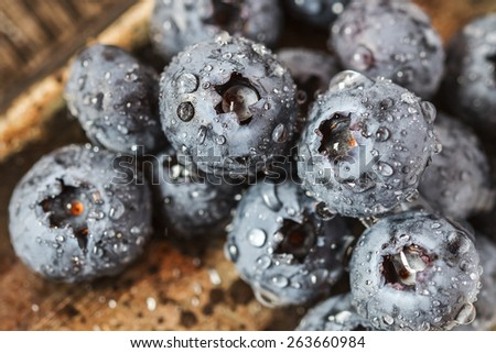 Wet fresh Blueberry with drops on wooden background. Selective focus - stock photo