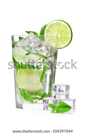Wet glass of mojito with ice cubes and mint leaves - stock photo