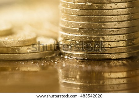 Wet gold coins close up - wealth concept