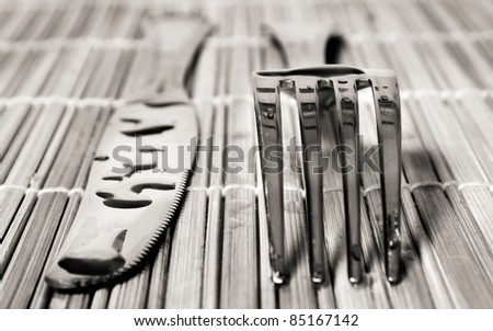 Wet knife and fork on a bamboo mat - stock photo