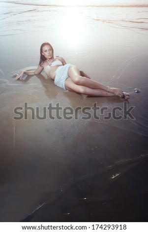 Wet lady laying at the evening beach. Vertical photo with natural colors and darkness