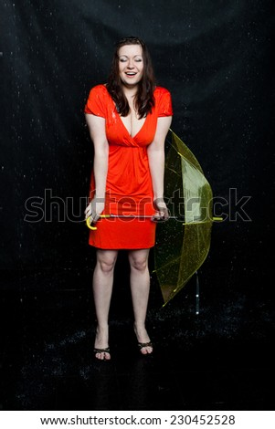 wet lass wearing red dress with umbrella stands under a rain - stock photo