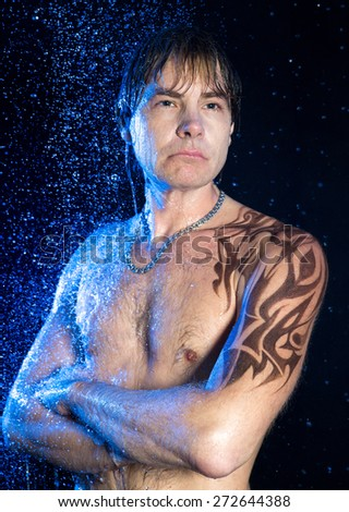 Wet Man in Aqua Studio. Close-up portrait of handsome man with graphic brown water-resistant tattoo on shoulder and neck, strong arms crossed on his chest. Fresh, aqua, water, clean, wet sexy body. - stock photo