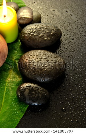 wet massage stones with green leaf and water drops
