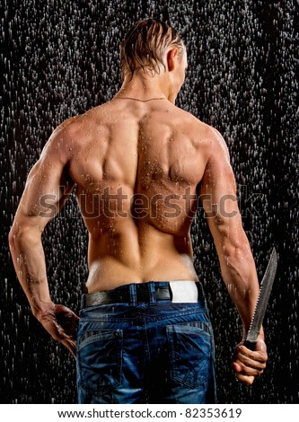 Wet muscle sexy young man back under the rain with knife in studio