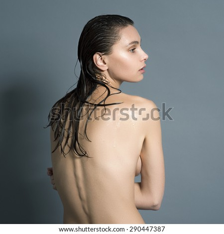 Wet naked girl standing in the studio with his back and arched her back visible spine