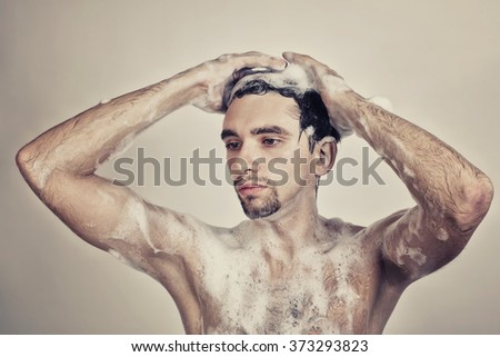 Wet naked young man in foam