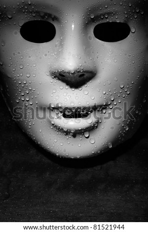 Wet plastic mask on a dark wooden background. Close-up monochrome photo - stock photo