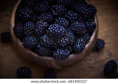 Wet ripe blackberries in wood bowl on rustic wooden table. Low light, dark and moody image.