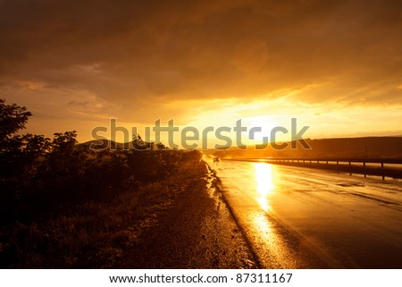 Wet road after rain and car in the distance - stock photo