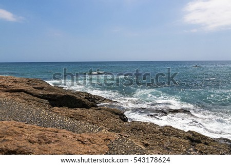 Wet rocky shoreline at Scottburgh beach against ocean white clouds and blue sky coastal landscape in South Africa