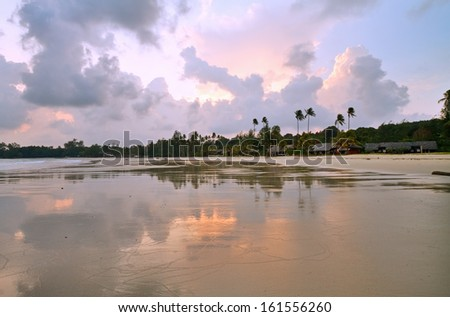 Wet sands coast with reflection on resort at sunset, Bintan, Indonesia. - stock photo