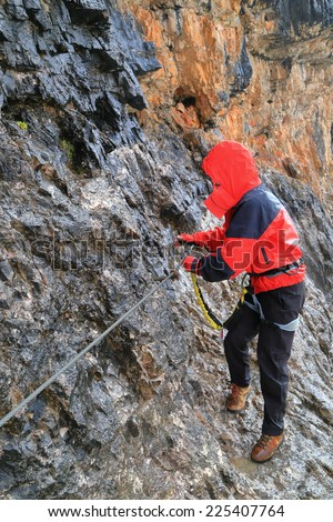 "Wet section of ""Lipella"" route with climber woman soaked by pouring water from the wall, Tofana massif, Dolomite Alps, Italy"