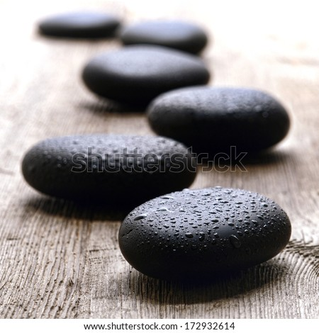 Wet smooth polished hot massage black stones covered with water drops and droplets in Zen style path on vintage wood table in relaxing wellness holistic spa for relaxation and good health rejuvenation