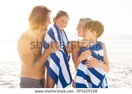 Wet son and daughter draped in towel embracing by parents after swim. Happy family at beach after swim in the tropical sea. Smiling father and mother drying children with a towels. - stock photo