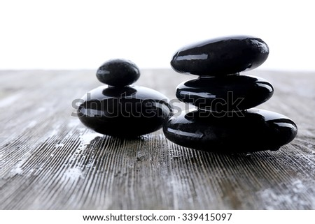 Wet spa stones on wooden table, closeup