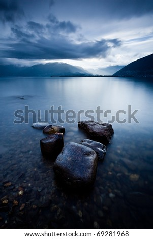 wet stones by lake shore under clearing storm light forming a V shape - stock photo