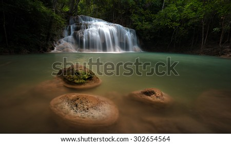 Wet stones in river stream in wild rainforest with scenic waterfall cascades at evening. Beautiful nature background - stock photo