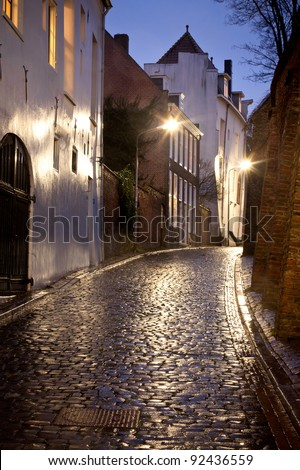 Wet street with old houses at night in Dutch city called Nijmegen. - stock photo