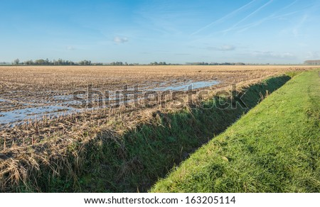 Wet stubble field with puddles and a ditch on a sunny day after the rain in the autumn season. - stock photo