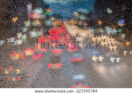 Wet the car window with the background of the night city traffic view. - stock photo