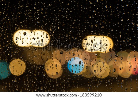 Wet window with background of city light. - stock photo