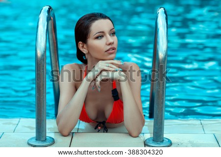 Wet woman dreaming on the edge of the pool, she was taking spa treatments. - stock photo