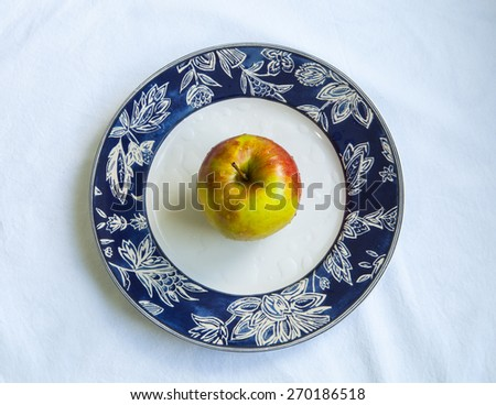 Wet yellow Apple on aplate, white background - stock photo