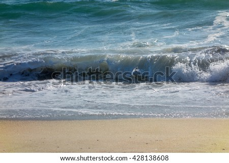 Wet yellow sand flattened by powerful rolling ocean waves - stock photo