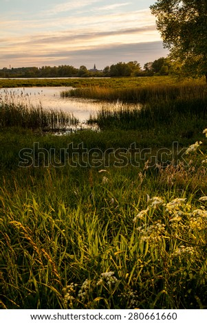 Wetlands around Nijmegen along Waal River during sunset  - stock photo