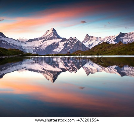 Wetterhorn peak reflected in water surface of Bachsee lake. Colorful summer sunrise in Bernese Oberland Alps, Grindelwald location, Innertkirchen, Switzerland, Europe.